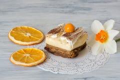 Torta con el physalis en una tabla de madera Adornado con la naranja secada y un narciso de la flor imagenes de archivo