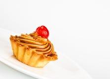 Torta con la ciliegia sul piatto Fotografie Stock