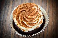 Torta con la crema, magdalena en Woody Background Foto de archivo libre de regalías