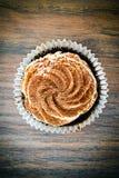Torta con la crema, magdalena en Woody Background imagenes de archivo