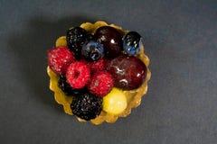 Torta con las bio frutas frescas, uvas, frambuesas, zarzamoras, foto desde arriba, fondo negro fotos de archivo