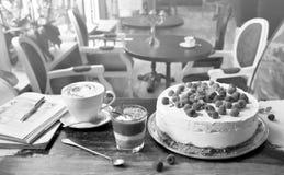 Torta con las frambuesas, el latte del café, el postre de la fresa y el libro imagen de archivo