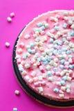 Torta con las pequeñas melcochas para la fiesta de cumpleaños en fondo rosado Foto de archivo libre de regalías