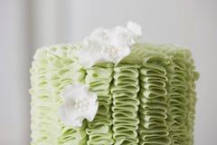 Torta con los volantes y Sugar Flowers de la pasta de azúcar Imagen de archivo