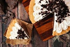 Torta crema del cioccolato, fine sulla scena con la fetta rimossa su legno scuro immagine stock
