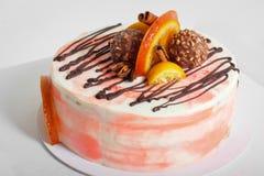 Torta cremosa deliciosa con el chocolate, rebanadas anaranjadas, palillo de canela Fotografía de archivo libre de regalías