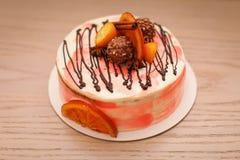 Torta cremosa deliciosa con el chocolate, rebanadas anaranjadas, palillo de canela Imagen de archivo