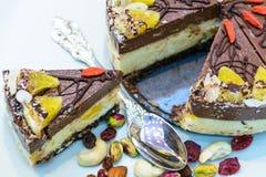 Torta cruda del vegano adornada con las frutas llenas coloreadas agradables, las nueces, las semillas de flor y los ingredientes  Fotografía de archivo libre de regalías