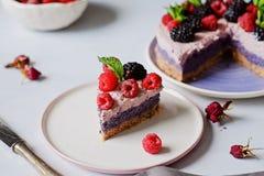 Torta cruda del vegano con las frambuesas y los bluberries en la tabla blanca fotografía de archivo libre de regalías