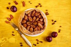 Torta das ameixas com passas em uma placa branca no fundo de madeira amarelo decorado com as três ameixas frescas, passas marrons Fotos de Stock