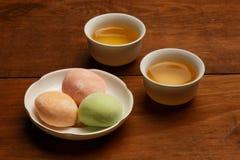 Torta de arroz colorida del mochi en la placa blanca y dos tazas w de la porcelana Fotos de archivo libres de regalías