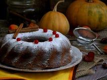 Torta de Bundt de la calabaza con los arándanos y las especias asperjados con el azúcar en polvo en fondo de madera Hornada hecha imagen de archivo libre de regalías