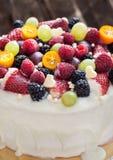 Torta de chocolate blanca adornada con las bayas y las frutas frescas Imagen de archivo libre de regalías