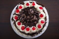 Torta de chocolate con crema y cerezas Fotos de archivo libres de regalías