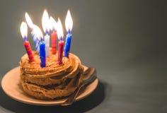 Torta de chocolate con crema y porciones de velas ardientes Imágenes de archivo libres de regalías