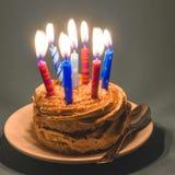 Torta de chocolate con crema y porciones de velas ardientes Foto de archivo