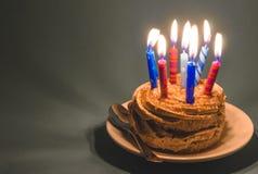 Torta de chocolate con crema y porciones de velas ardientes en un fondo oscuro Foto de archivo libre de regalías