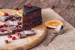 Torta de chocolate con el chocolate con leche, las semillas de la granada y las rebanadas anaranjadas en el paño de la lona foto de archivo