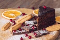 Torta de chocolate con la granada, el chocolate amargo y las galletas imagenes de archivo