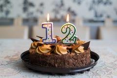 Torta de chocolate con las velas el día doce de nacimiento Imagen de archivo libre de regalías