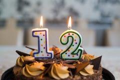 Torta de chocolate con las velas el día doce de nacimiento Foto de archivo libre de regalías
