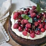 Torta de chocolate con mascarpone en fondo rústico con las frambuesas, los arándanos y las hojas de menta fotos de archivo