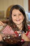 Torta de chocolate de hornada de la muchacha Imagen de archivo