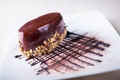 Torta de chocolate del postre con el desmoche y las nueces en una placa blanca Imagen de archivo