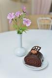 Torta de chocolate deliciosa cerca con las flores en la tabla blanca en café Fotos de archivo libres de regalías