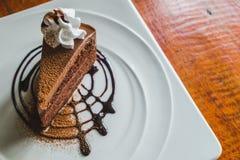 Torta de chocolate deliciosa con el wipcream en la placa en la tabla de madera Fotos de archivo