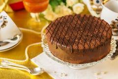 Torta de chocolate en el disco, las tazas, los platillos y las cucharas grandes para el té fotografía de archivo libre de regalías