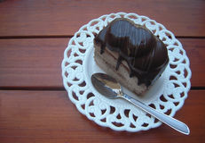 Torta de chocolate en una placa blanca con una cucharilla Foto de archivo libre de regalías