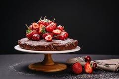 Torta de chocolate toscana con las fresas y las cerezas Imagen de archivo