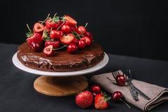 Torta de chocolate toscana con las fresas y las cerezas Foto de archivo