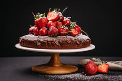Torta de chocolate toscana con las fresas y las cerezas Imagenes de archivo