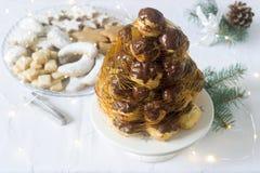 Torta de Crockembush y galletas de la Navidad en una decoración de la Navidad con una guirnalda de las ramas y de los conos del a Fotografía de archivo