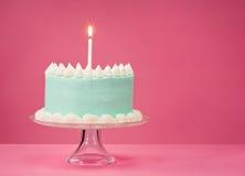 Torta de cumpleaños azul sobre fondo rosado Imagen de archivo libre de regalías