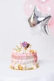 Torta de cumpleaños con adornado con los caramelos, piruleta, melcochas Color en colores pastel rosado Globos en fondo Fotografía de archivo libre de regalías