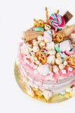 Torta de cumpleaños con adornado con los caramelos, piruleta, melcochas Color en colores pastel rosado Globos en fondo Primer Fotos de archivo libres de regalías
