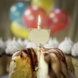 torta de cumpleaños con cierre conceptual de la tarjeta y del candel de felicitación encima de la foto Imágenes de archivo libres de regalías