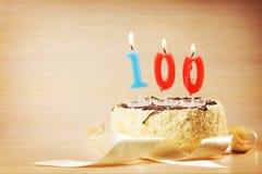 Torta de cumpleaños con la vela ardiente como número ciento Fotografía de archivo