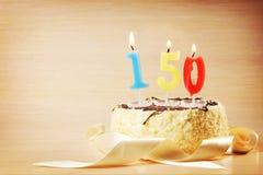 Torta de cumpleaños con la vela ardiente como número ciento y cincuenta Imagenes de archivo