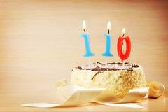 Torta de cumpleaños con la vela ardiente como número ciento y diez Fotos de archivo libres de regalías