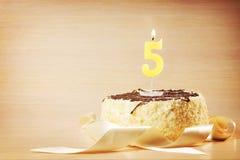 Torta de cumpleaños con la vela ardiente como número cinco Imagen de archivo