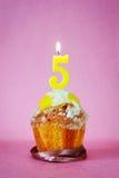 Torta de cumpleaños con la vela ardiente como número cinco Imágenes de archivo libres de regalías