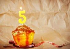 Torta de cumpleaños con la vela ardiente como número cinco Imagenes de archivo