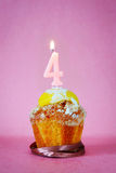 Torta de cumpleaños con la vela ardiente como número cuatro Fotografía de archivo