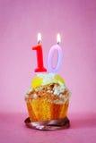Torta de cumpleaños con la vela ardiente como número diez Foto de archivo