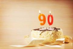 Torta de cumpleaños con la vela ardiente como número noventa Fotos de archivo