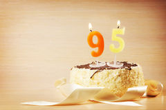 Torta de cumpleaños con la vela ardiente como número noventa y cinco Fotografía de archivo